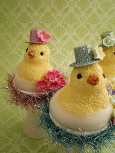 """Each glittery chick is sitting atop a creamy, stylish ceramic egg cup """"float"""", wrapped in a wool roving nest decorated with flowers and wrapped in shiny tinsel. Their perky Easter hats are covered in glitter and also decorated with a paper flower."""