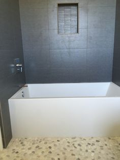 Pebble and rock bathroom tile floor. Large format wall tile in this rustic shower