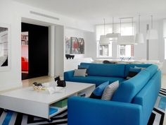 An electric blue sectional is the centerpiece of the loft's main living area. Its clean lines and bold upholstery fit in perfectly with the home's modern, color-centric aesthetic.