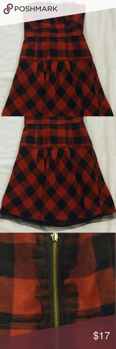 AEO red & black buffalo check/plaid mini dress This is a strapless red & black buffalo check plaid dress by American Eagle Outfitter. With black tulle trim at bottom hem and ruffles around exposed back zip. Lightly boned, fitted bodice. 65% polyester/35% rayon.  PLEASE NOTE: This is in very good used condition; however, there's a small cut in one of the ruffles on back zip (see pic #3.) American Eagle Outfitters Dresses Mini