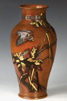 A majestic bronze and multi-metal baluster vase applied with colored lacquers and sculpt with the quintessential Japanese imagery of a plover-in-flight over clusters of reeds and foliage. Its classic form and design with overlays of gold, shakudo and lacquer in high relief enhance the visual drama and technological perfection of the piece. Suzuki Chokichi signature and kako double-mountain mark on base. Height, 10.75''. Meiji Period.