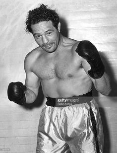 American boxer Max Baer (1909 - 1959), the 1934 world heavyweight champion poses in a fighting stance, wearing his gloves and boxing shorts. - #maxbaersr  #maxbaer