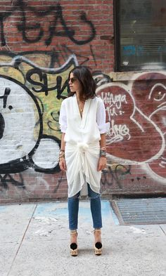 Raw hem jeans paired with a white button down, sheer sarong, and fun pom-pom heels.