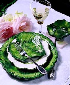 Vietri Dinnerware - the dinner plate looks like the classic collection and the leaf on top might be either the classic or fresca collection.  Contrast with the white is pretty.  The Vietri Foglia and Foglia Fresca collections represent Italian Majolica with its embodiment of nature with its vivid shades of green that blanket bas-relief leaves made from white clay. Each unique piece is handmade in Italy.