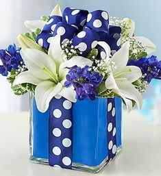 A buoyant blue and white polka dot ribbon encircles a hand-crafted cube vase arrangement of while lilies, blue delphinium and fresh greens, bringing to mind a beautifully wrapped gift box. #denverflorist #denverflowers #denverflowerdelivery