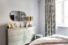The opposite side of the room is a touch more subdued with a metal dresser and simple mirror.