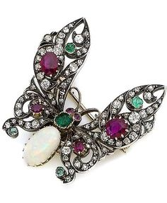 A ruby, emerald, opal and diamond butterfly brooch The pierced wings set throughout with rose, old brilliant-cut and cushion-shaped diamonds, with oval-cut ruby and emerald accents, the body collet-set with a cushion-shaped emerald and an oval cabochon opal, old brilliant and cushion-shaped diamonds approx. 0.65ct total, detachable brooch fitting, length 4.1cm