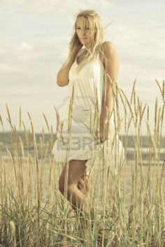 a beautiful young blond at the beach wearing a white summer dress Stock Photo