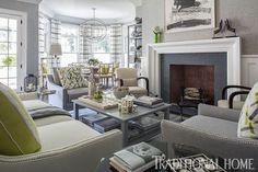 """Hampton Designer Showhouse 2013   Traditional Home   Keeping Room by Patricia Fisher  With its sumptuous seating and subtle cream-and-gray palette, the keeping room is an ideal spot to spend the weekend. """"It's user-friendly, but still sophisticated,"""" says designer Patricia Fisher. Shots of chartreuse hint at the beautiful Hampton views beyond the bay windows. The linen sofa, matching club chairs, tiered coffee table, and silver orb chandelier are by Ballard Designs."""
