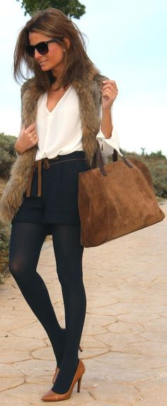 Wear dress shorts over black tights and layer with a fur vest to make your shorts work for fall.