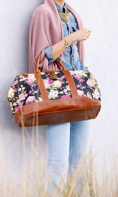 Doctor-inspired weekender bag in a rich floral print with adjustable cross body strap and antique gold-toned hardware.