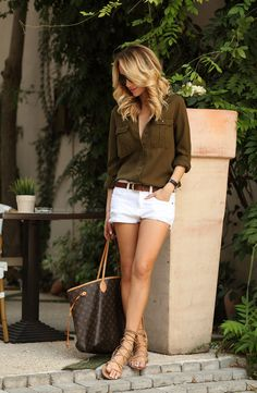 White shorts, brown belt, button down shirt and a statement bag.