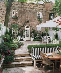 stone steps; patio furniture; umbrella; plants; big tree; and really cool house too