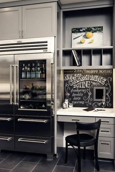 Gray kitchen features a gray built-in desk topped with white quartz under a black chalkboard backsplash and pigeon hole cubbies next to a Viking glass front fridge.