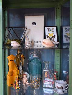 Eclectic Modern Bohemian interior decor, cabinaet curisosity shells, foo dog