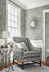 Like the black and white geometric fabric on the chair. Interesting how it plays against the panther print wallpaper. Thibaut Design