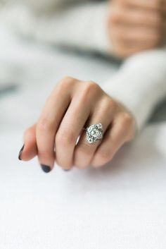 The Angelica ring is a Vintage Engagement Ring from the Edwardian Era circa 1910! This ring centers a GIA Certified old European cut diamond weighing 1.20 carats of I color, SI2 clarity. The diamond is set in a platinum millegrain edging. To the north and south is an old European cut diamond, each weighing approximately 0.27 carats. To each side of the center stone is an additional old European cut diamond. The setting has lovely, scrolling, open metal work and lace-like filigree