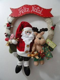 """Guirlanda de Natal Papai Noel e Rena com presentes.  A Rena segura uma plaquinha e escrita: """"Entre com o coração feliz""""  Tamanho aproximado: 52 cm (atura) x 42 cm (largura) - contando as perninhas que ficam para fora da base da guirlanda. R$ 165,00"""