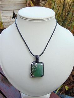 Made from a rectangle shaped aventurine cabochon this pendant has been wire wrapped in a prong setting to make the most of this beautiful green stone. The wire its made from is silver filled copper that has a 10% plating of silver which is 99.95% pure. A patina has been applied to give