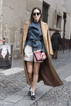 street style: Paris Fashion Week Fall 2014... Shorts become Fashion-Week chic with a pair of oxfords and a smart overcoat.
