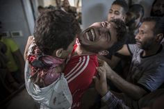 Un hombre palestino llora mientras sujeta el cuerpo sin vida de su hermano pequeño muerto en un bombardeo israelí en el puerto de Gaza, en el depósito de cadáveres del hospital Shifa. Cuatro niños palestinos murieron el 16 de julio de 2014, en un ataque aéreo israelí en la franja de Gaza, que hirió a otra decena de menores, informó el portavoz del Ministerio de Sanidad, Ashraf Al Qedra. | Oliver  Weiken/EFE.