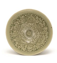 A 'YAOZHOU' CELADON 'FLORAL' BOWL NORTHERN SONG / JIN DYNASTY, of conical form with deep rounded sides rising from a neatly cut foot to an everted rim, moulded on the interior with a central chrysanthemum flower encircled by a meandering scroll. 19.2 cm