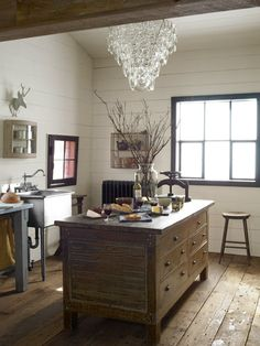 Give a room more than one purpose. Equipped with an antique island and an industrial sink, the corner of this carriage house functions as an art studio, as well as an ad-hoc kitchen. #decoratingtips