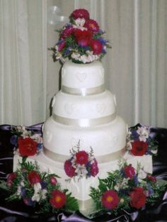 Red and White with purple accents.  White ribbon borders trimmedd with pearls.  White lace hearts decorate the sides of each tier.  Floral sprays decorate the square base tier and a floral topper adorns the top tier.