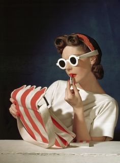 From Vogue, 1950s. Everything is perfect: purse, hair, sunglasses!