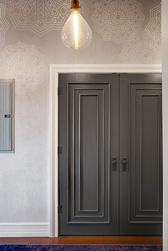 Custom moldings were introduced here as well, while the doors to the entry, extra bedroom, and powder room were either replaced or trimmed in matching moldings and painted a saturated gray hue to complement the lighter walls.