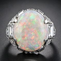 A gorgeous oval white opal - weighing between nine and ten carats -  sits snug in a magnificent, original Art Deco platinum mounting with 2.75 carats of sparkling diamonds. An Art Deco treasure, circa 1930.