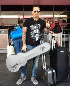 Guns N Roses lead guitarist Dj Ashba, with guitar in tow, chatting with fans at McCarran International Airport Saturday while waiting for a flight to LA for tour rehearsals.