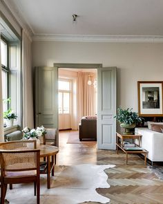 colored doors and window trim in a light palette room. pretty herringbone floors.