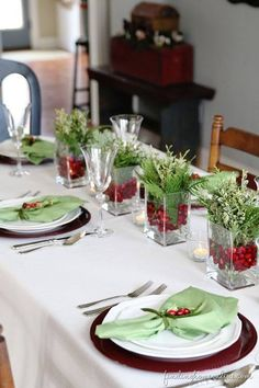 Simple but gorgeous table setting; the vases filled with cranberries and fresh greenery look wonderful! #christmasdecor