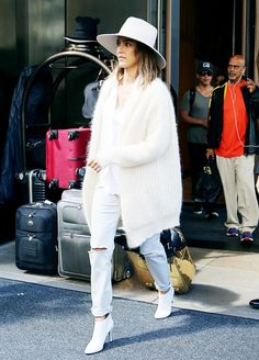 Jessica Alba wears a white t-shirt,  mohair cardigan, boyfriend jeans, white booties, and a fedora