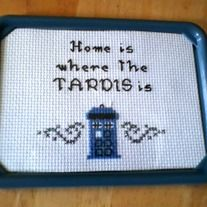 """Inspired by Doctor Who, this cross stitch sampler reads """"Home is where the TARDIS is"""" complete with a mini TARDIS Police Box.  This funny cross stitch sampler is set in a 3 x 5 inch photo frame. It has a magnet attached to the back, but can also be used as a hanging or free standing frame.  T..."""