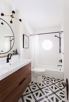 Graphic tile floor, clean white countertops and subway tile. So much to love about this bathroom!