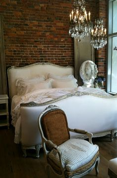 Pale pink and white French bed with a sparkly chandelier against the brick wall to add romance and sparkle.