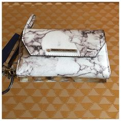 "Rebecca Minkoff marble print Monroe tech Wallet Rebecca Minkoff marble print Monroe tech Wallet.  A marbled finish brings a touch of modern elegance to a sleek wristlet, while the interior phone pocket ensures easy access to your tech. Fits most smartphones. Optional wrist strap. Top zip closure. Exterior snap-flap pocket. Interior zip, smartphone and currency pockets; six card slots.  Dimensions 8 x 4.9 x 1.6"". Can fit up to an iPhone 6.  PVC with leather trim.  Brand new with tags still…"