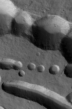 Ascraeus Pits - This Mars Global Surveyor (MGS) Mars Orbiter Camera (MOC) image shows collapse pits on the northern flank of the giant Tharsis shield volcano, Ascraeus Mons. Details in rock and dust are seen when this image is examined at its full, 1.5 meters (5 ft) per pixel resolution. Credits: NASA/JPL/Malin Space Science Systems | via RedOrbit.com