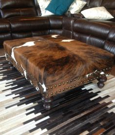 Further proof that cowhide works for decor styles from cabin rustic to traditional elegant.  This customizable ottoman upholstered with genuine hair-on-hide will make a dramatic statement in your living or family room.  Shown in tricolor cowhide. Choose from several different cowhide color combinations, as well as whatever dimensions best fit your space. It is built upon order to your specs.