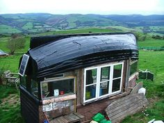 This is what you get when you make a roof from a 100 year old boat, walls from a 70 year old caravan and windows from a 400 year old farm. A neat tiny shed. http://tinyhouseblog.com/tiny-house-concept/my-boat-roofed-shed