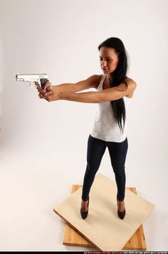 PHOTO OF WOMAN YOUNG ATHLETIC FIGHTING WITH GUN STANDING POSES CASUAL LATINO