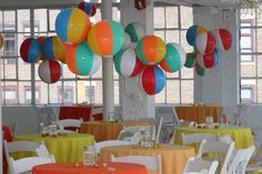 "For an indoor summer-themed gathering, Swank producers used beach balls to create playful ""chandeliers."" Tables were covered in summery yellow and orange linens."