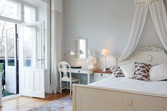 Dormitorio clásico en blanco y con dosel. Ventanas amplias.