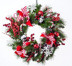 This wreath is decorated with a variety of traditional Christmas floral and ornaments including pine, snow flakes, candy canes, red striped ribbon and bright red berries. $159