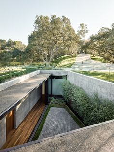 """The Oak Pass Main House uses an """"upside down"""" program, with public spaces above the bedrooms, which are buried into the hill and beneath a green roof of edib..."""