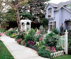 A scalloped white picket fence and arbor surrounded by a lush garden: #bhg