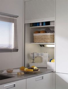 SANTOS kitchen   Solutions for the laundry    Worktop-mounted rolling shutter unit. The interior of the roller-shutter unit, apart from offering an additional workspace, has electrical sockets and its own lighting system that makes it possible to use small electrical appliances without having to move them. We can store small electrical appliances, threads, wool and other sowing accessories which can all be tidied away and out of sight when the roller-shutter is shut