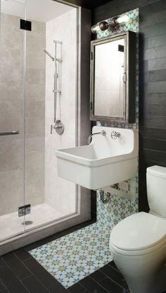 baño pequeño, con pie ducha y mampara de vidrio,  baldosas de cerámica que imitan la pizarra en paredes y techo, baldosas hidráulicas. presupuestON.com